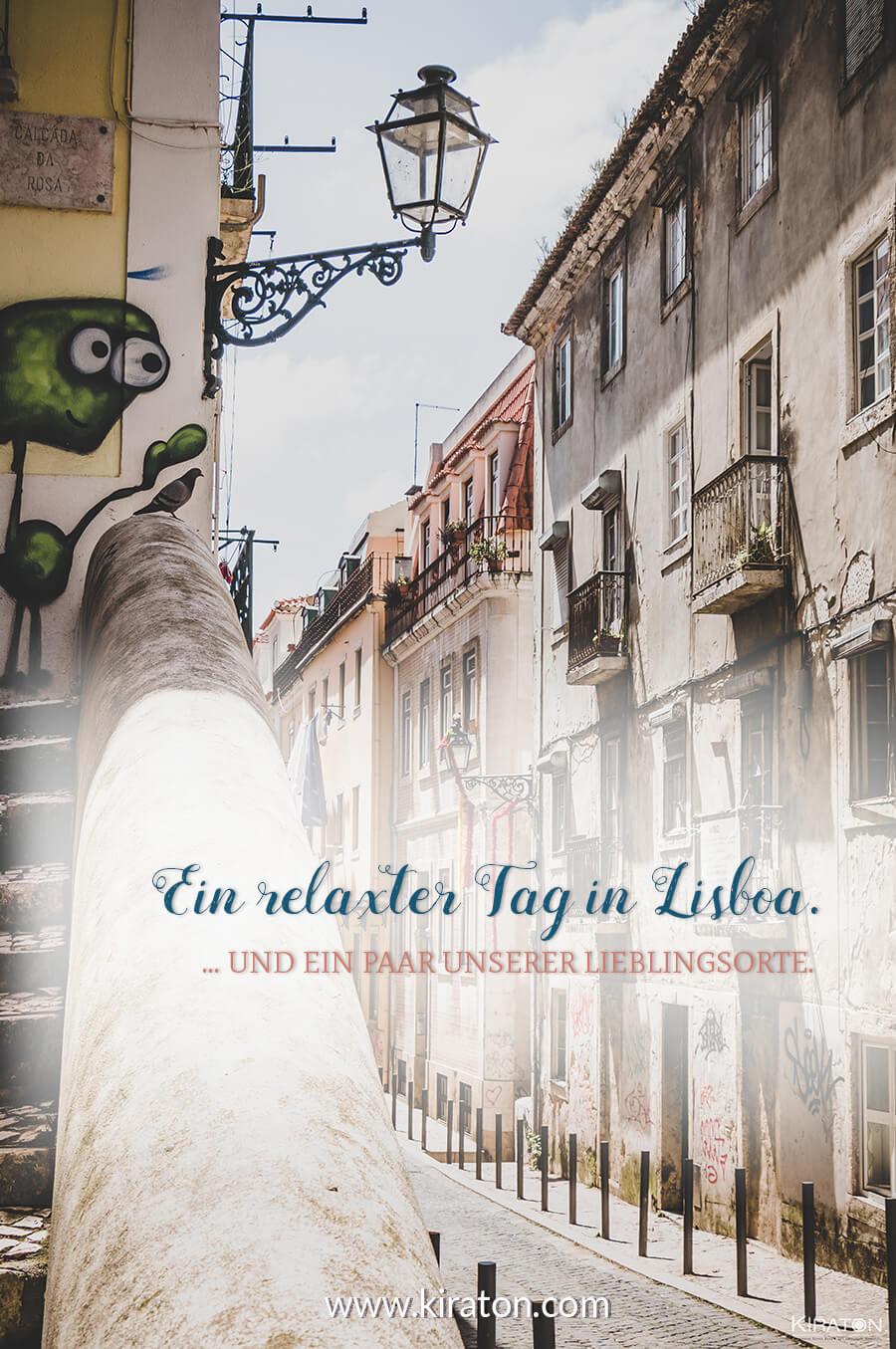 Blick in eine Gasse in Lisboa. Eine Treppe links im Bild leicht angeschnitten. Oben ist ein grünes Wesen an die Wand gesprüht. Es scheint hinunter zu blicken auf die Straße.