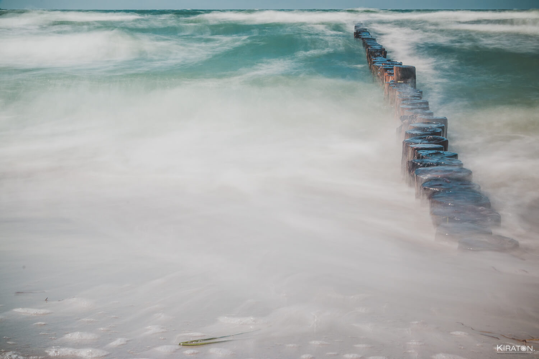 Langzeitbelichtung auf Buhnen, die von Wellen umspielt werden.